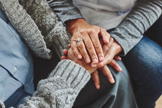 Pair of hands Clasped Together Showing Comfort in a time of bereavement