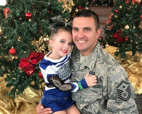 Air Force father holding his daughter who participates in Our Military Kids programs