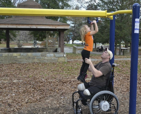Wheel-chair bound amputee military father helping his daughter on the playground