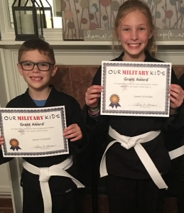 Two Our Military Kids children proudly holding their grant award certificates