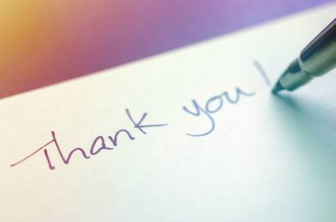 Thank you on a post-it note written with a pen
