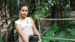 Girl holding a potted tree sapling in Peru